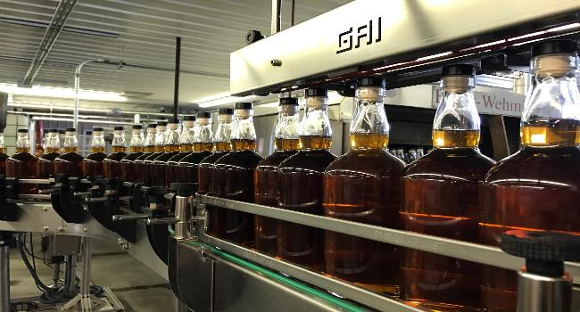 A line of whiskey bottles in a Distillary