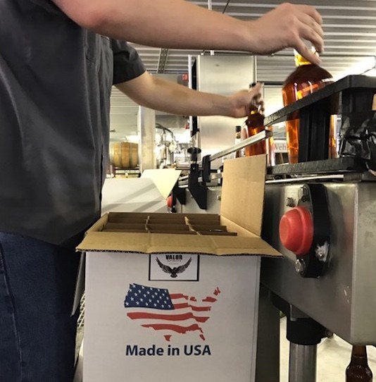 A man putting two whiskey bottles into a cardboard box that has an American flag on it